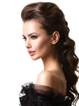 Bel viso di una giovane donna sexy con i capelli lunghi in posa sul muro bianco