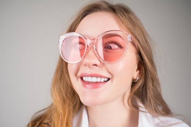 Beautiful face of young smiling woman in sunglasses