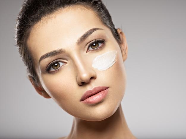 Bel viso di giovane donna con crema cosmetica striscio sul viso vicino all'occhio. concetto di cura della pelle. concetto di trattamento di bellezza. Foto Gratuite