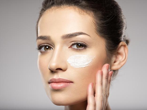 Bel viso di giovane donna con crema cosmetica striscio sul viso vicino all'occhio. concetto di cura della pelle. concetto di trattamento di bellezza.