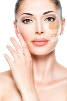 Beautiful face of  young woman with cosmetic foundation on a skin.   beauty treatment concept