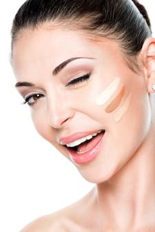 Bel viso di giovane donna con fondotinta cosmetico su una pelle. concetto di trattamento di bellezza