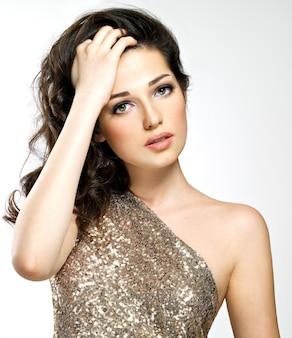 Bel viso della giovane donna con i capelli castani ricci