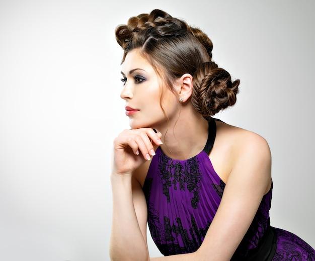 Bel viso di giovane donna con acconciatura alla moda con design trecce, pose in studio