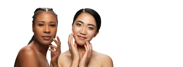 清潔で新鮮な肌を持つ2人の若い女性の美しい顔。広告用のコピースペース付きのチラシ。美容、ヘルスケア、化粧品の概念。手入れの行き届いた肌を持つ魅力的なアフリカ系アメリカ人とアジアの女性。