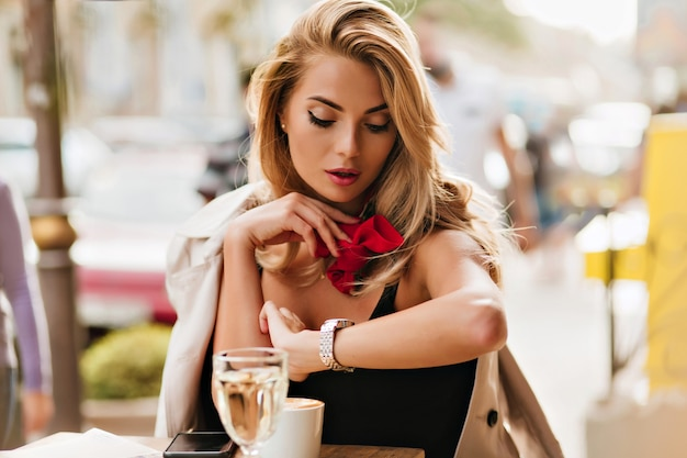 Bella donna bionda guardando orologio da polso mentre beve il caffè al ristorante all'aperto. ritratto di signora seria con sciarpa rossa in attesa di fidanzato che è in ritardo.