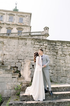 Beautiful fairytale newlywed asian couple holding hands and kissing near old medieval castle