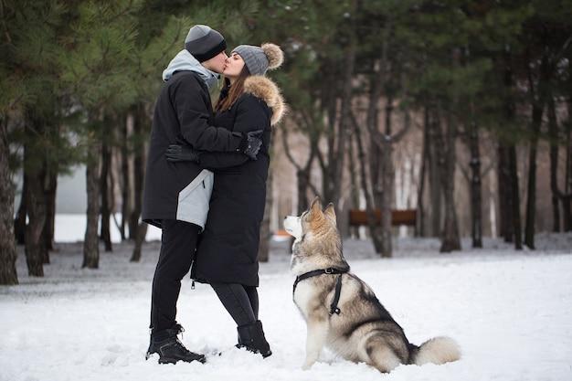 Красивая семья, мужчина и девушка в зимнем лесу с собакой. играйте с собакой сибирский хаски.
