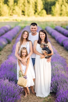 Красивая семья и их маленькая собачка в сиреневом поле. летнее фото в фиолетовых тонах ..