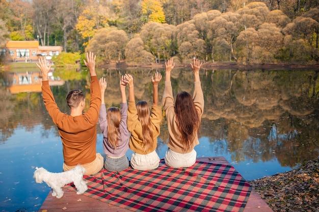 湖の近くの秋の暖かい日に美しい家族