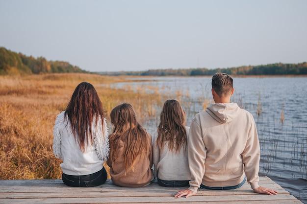 Красивая семья в осенний теплый день возле озера
