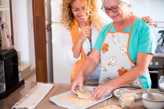 家庭で料理をし、一緒に楽しんでいる美しい家族-クーキーと魚の調理方法を示すおばあちゃん-屋内ライフスタイル-白人女性と成熟した女性が楽しむ-白人