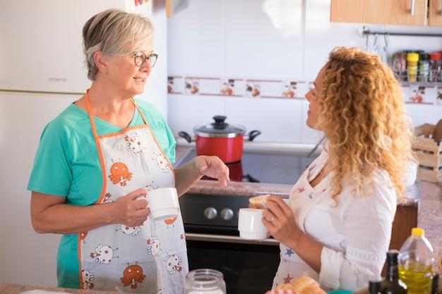 家庭で美しい家族が料理をし、一緒に楽しんでいます-おばあちゃんがクーキーと魚を調理する方法を示しています-屋内ライフスタイル-白人女性と成熟した女性が楽しんでいます