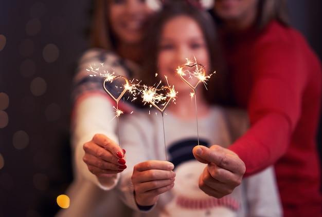 クリスマスを祝い、花火を持つ美しい家族