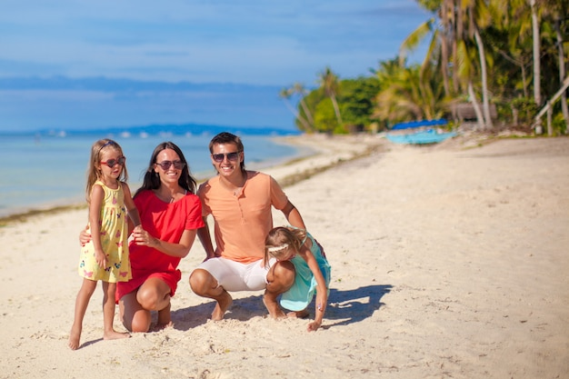 Beautiful family of four have fun on the beach in philippines