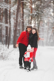 A beautiful family have fun in the winter snowy forest. mother, father and daugther in red clothes enjoying day outdoors. holidays, christmas, happiness together, childhood in love.