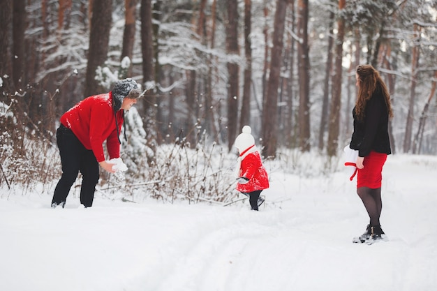 A beautiful family have fun in the winter snowy forest. mother, father and daugther in red clothes enjoying day outdoors. holidays, , happiness together, childhood in love.