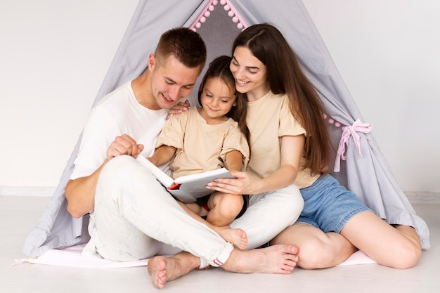 Красивая семья, весело проводящая время в палатке