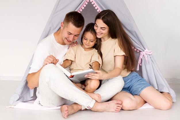 Bella famiglia che ha un momento carino insieme in una tenda