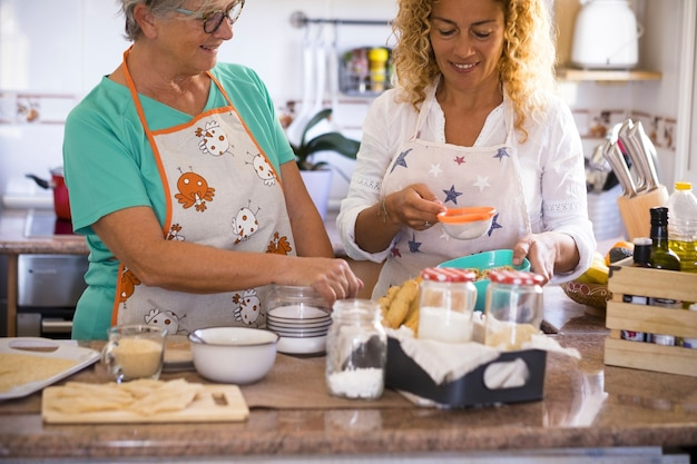Beautiful family at home cooking and having fun together - grandma showing how to cook coockies and fish - indoor lifestyle - caucasian woman and mature woman enjoy