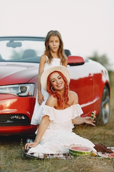 公園の美しい家族。白いドレスと帽子の女性。毛布の上に座っている娘と母。