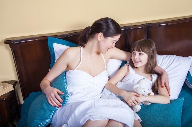 Красивая семья утром. мать и дочь смотрят друг на друга и зубасто улыбаются. студийный снимок