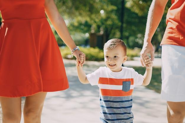 通りと公園を歩いている赤い美しい家族