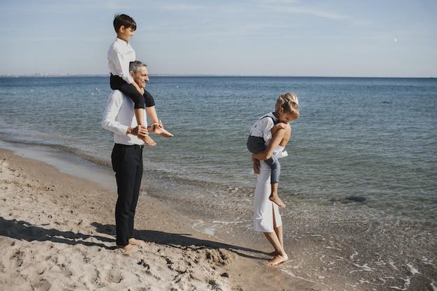 Красивая семья гуляет по береговой линии, родители и два сына, в солнечный летний день