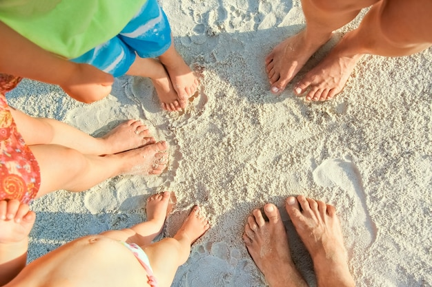 Beautiful family legs on the sand by the sea