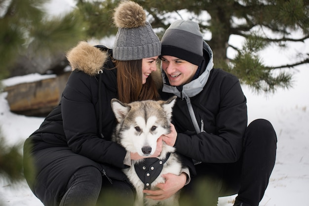 Beautiful family, a man and a girl in winter forest with dog. play with the dog siberian husky.