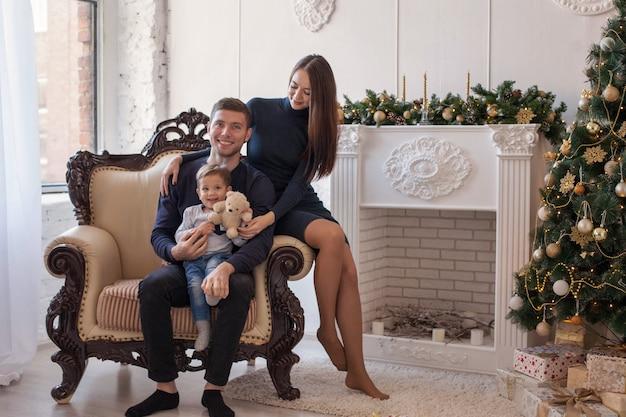 아름다운 가족 엄마, 아빠와 아기는 벽난로 옆에 선물과 화환이있는 새해 트리에서 크리스마스를 축하합니다.