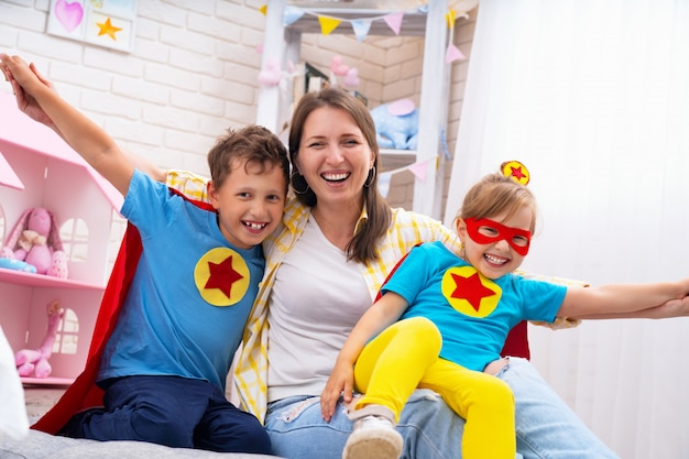 Beautiful family mom and daughter with son dressed in costumes of super heroes