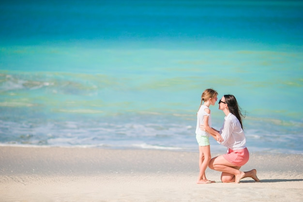 Beautiful family of mom and little girl on beach vacation