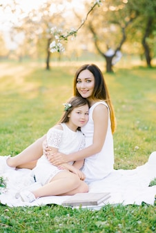Beautiful family mother and daughter in white dresses sitting on a white plaid in the flowering gardens in the spring