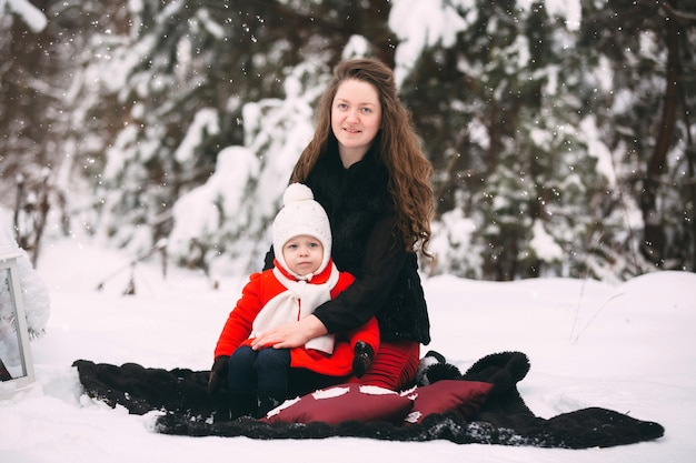 Beautiful family of mother and her little daughter enjoying snowy winter day in forest
