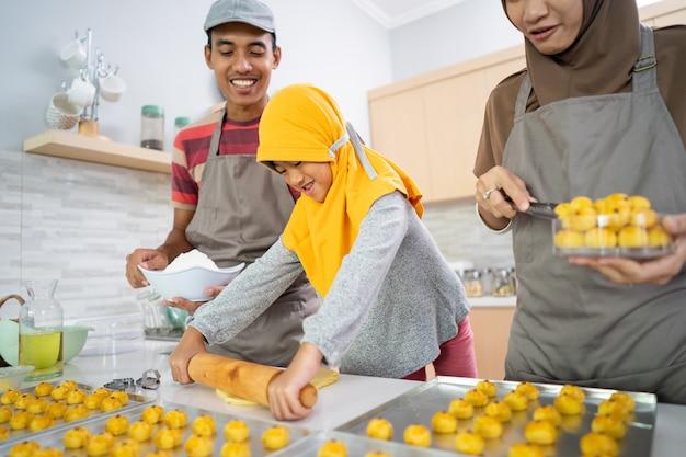 自宅で一緒にインドネシアの伝統のnastarパイナップルケーキを作るイスラム教徒の美しい家族