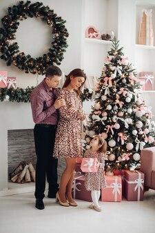Красивая семья из трех человек вместе встречает новый год возле елки с большим количеством подарков