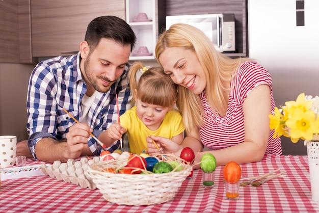 Красивая семья с ребенком раскрашивает пасхальные яйца