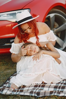 Beautiful family in a park. woman in a white dress and hat. mother with daughter sitting on blanket.