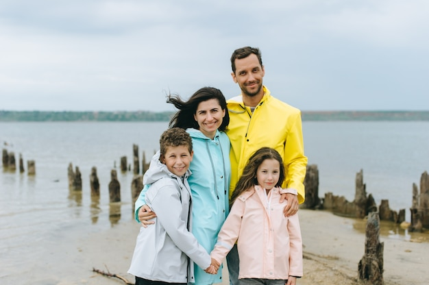 Beautiful family portrait dressed in colorful raincoat near the lake