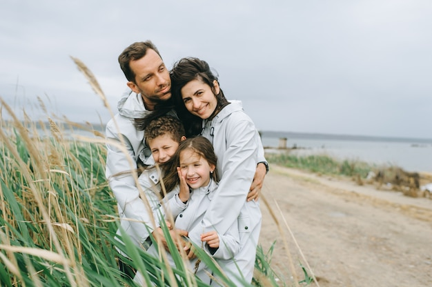 Beautiful family portrait dressed in raincoat near the lake