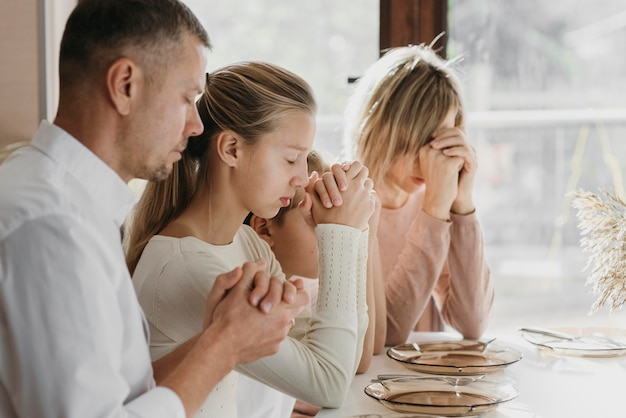 Beautiful family praying together before eating