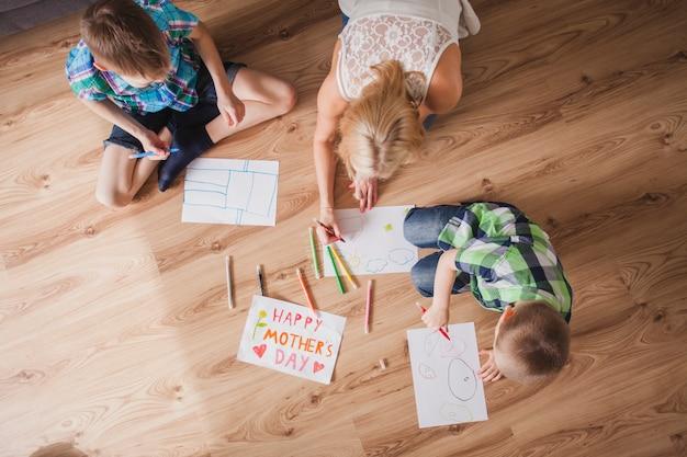 彼女の子供たちと一緒に描く母親の美しい家族の風景