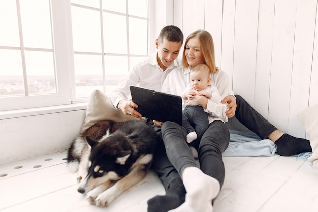 Beautiful family spend time in a bedroom with a tablet