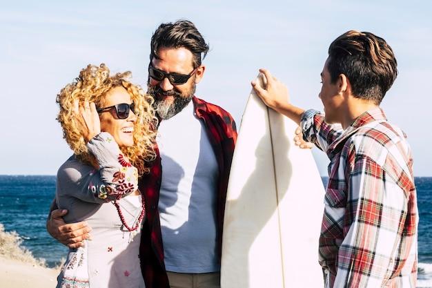 화창한 날과 서퍼 십대와 함께 해변에서 영원히 함께하는 아름다운 가족 - 서핑 테이블 및 행복한 사람들과 함께 이야기 - 여름 휴가 - 후면보기