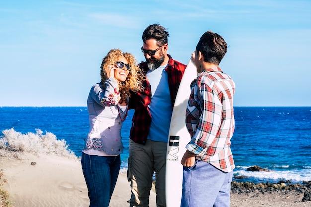Красивая семья вместе навсегда на пляже с солнечным днем и подростком-серфером - разговаривают вместе со столом для серфинга и счастливыми людьми - летние каникулы - вид сзади
