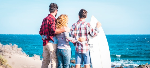 Beautiful family together forever at the beach with a sunny day and surfer teenager - talking together with surf table and happy people - summer vacation - rear view - happy family hugged together