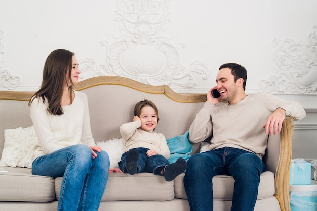 携帯電話を使っている美しい家族