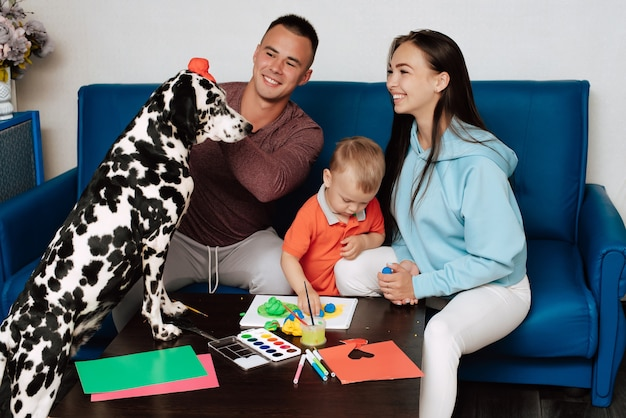 Beautiful family with a dog painting with their kid