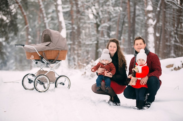 A beautiful family with retro pram walks through the winter snowy forest. mother, father, daughter and baby son enjoying day outdoors. holidays, christmas, happiness together, childhood in love.